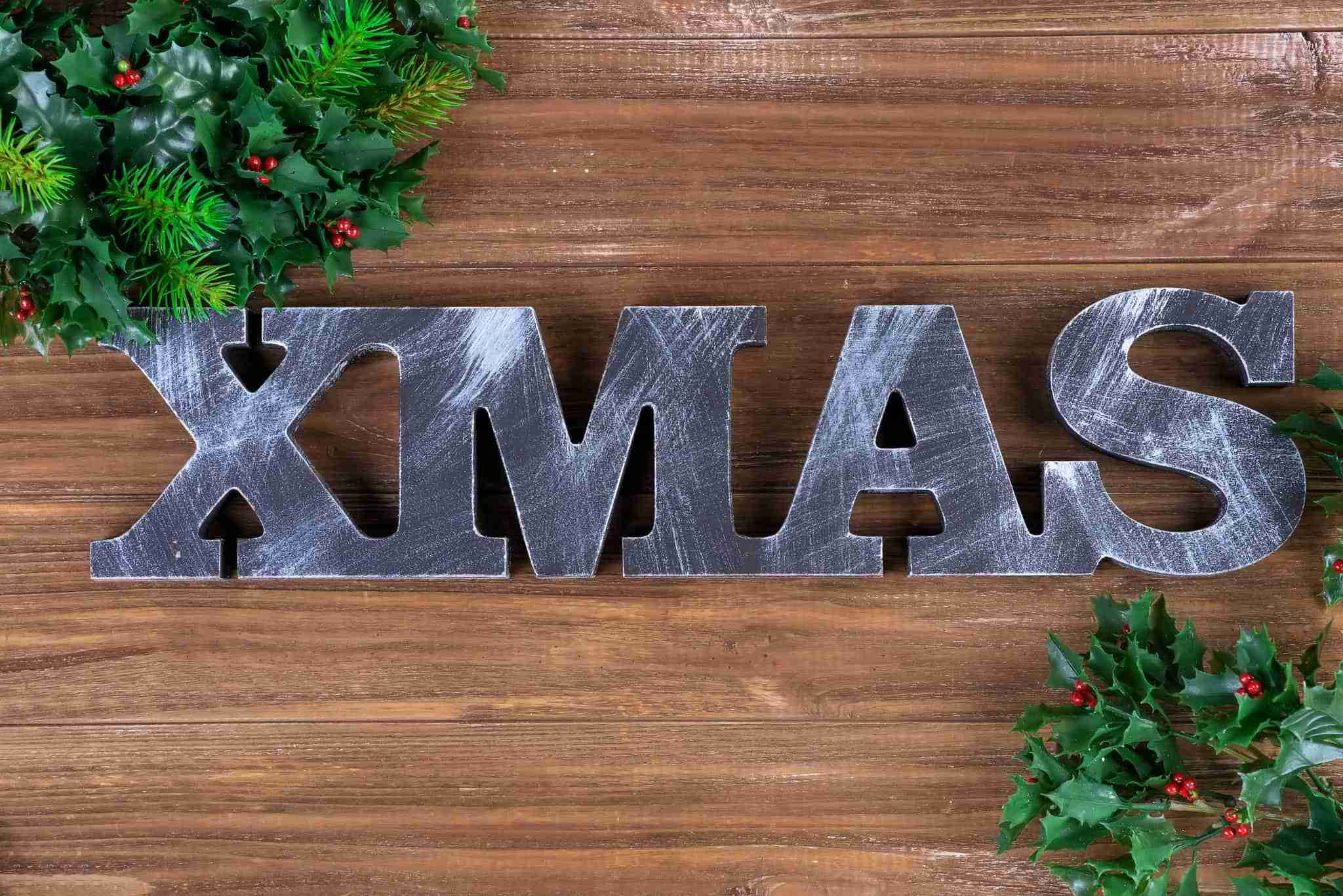 Wooden letters XMAS with fit branches on a wooden background